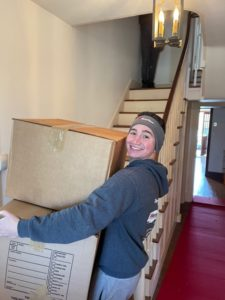 man smiling moving boxes into a home