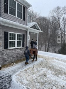 men moving items into a home with snow on the ground